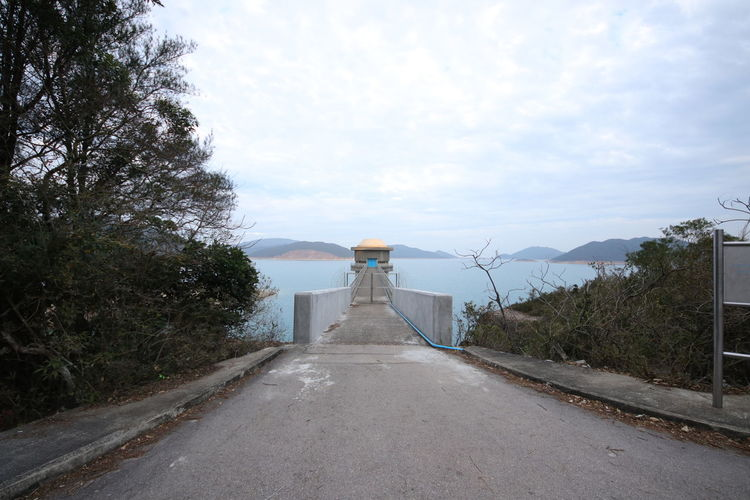Road leading towards pier at high island reservoir