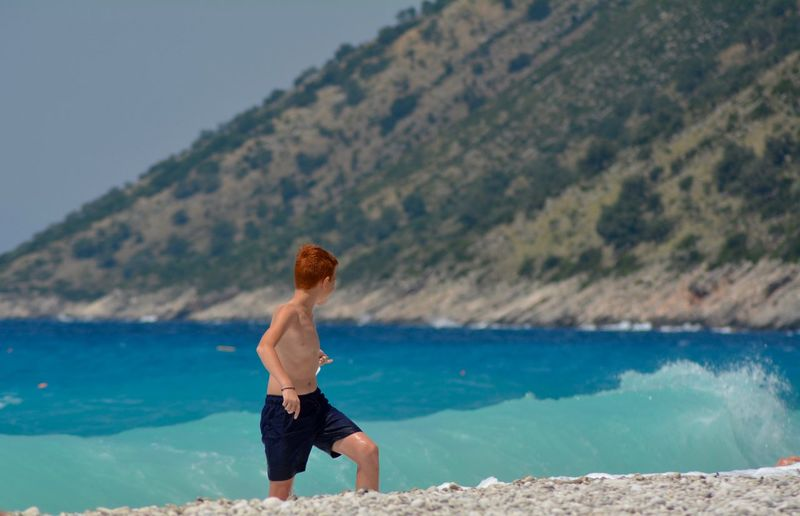 Shirtless boy running on shore at beach
