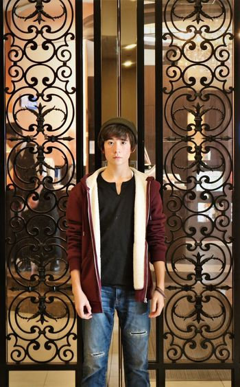 Portrait Of Teenage Boy Standing Against Wrought Iron