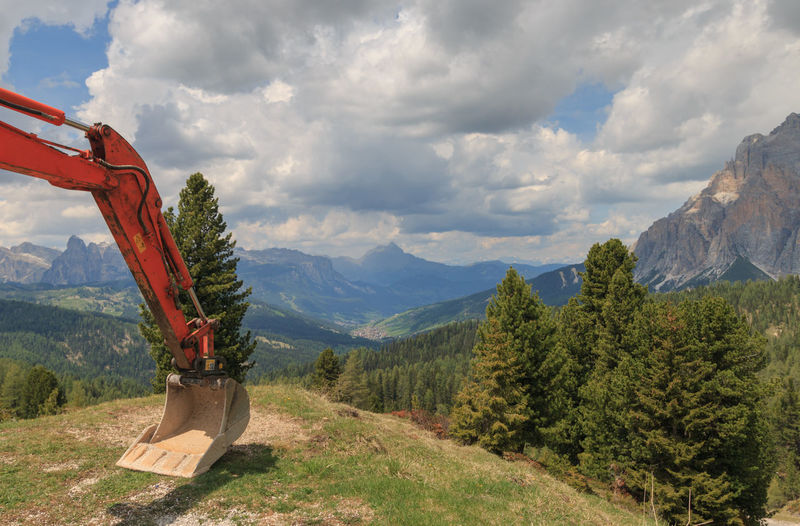 Panoramic view of val badia with shovel of excavator