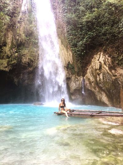 Woman in bikini sitting on wooden raft against waterfall