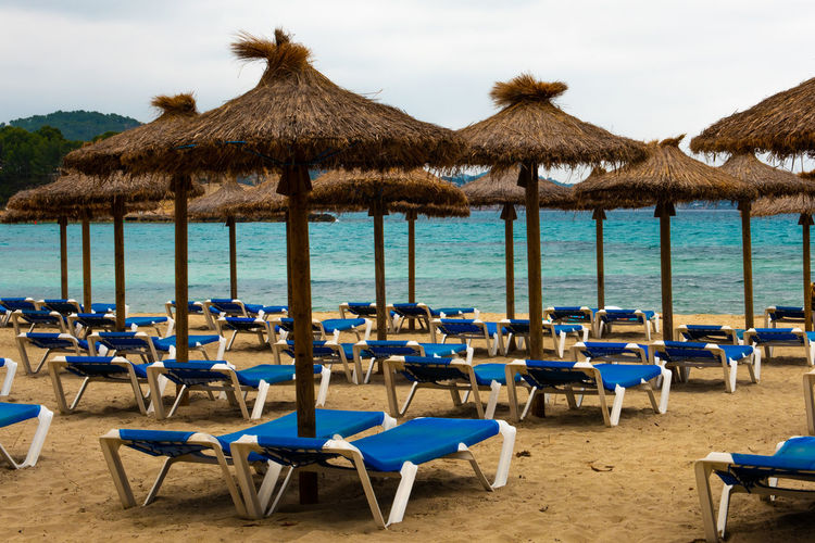 Mallorca SPAIN Summertime Absence Architecture Baleares Balearic Islands Beach Beach Chairs Chair Day Go-west-photography.com Land Nature No People Outdoors Parasol Roof Sand Scenics - Nature Sea Seat Sky Summer Table Thatched Roof Tranquil Scene Tranquility Travel Destinations Water