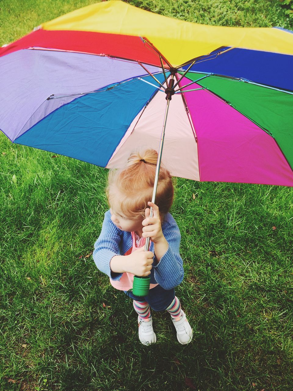 Full Length Of Cute Baby Girl With Colorful Umbrella Standing On Grassy Field At Park
