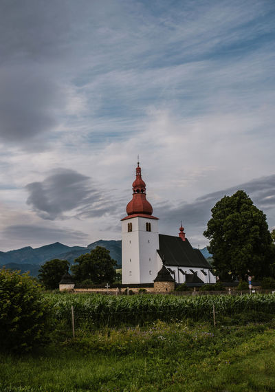 Church on field by building against sky