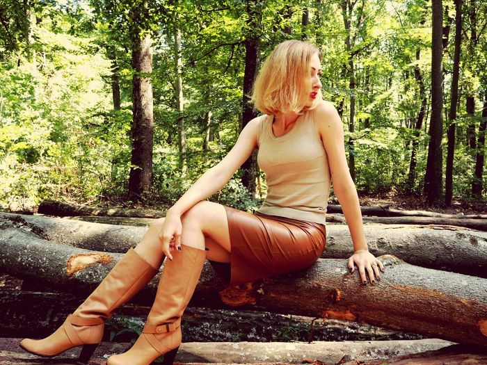Woman looking away while sitting on fallen tree at forest