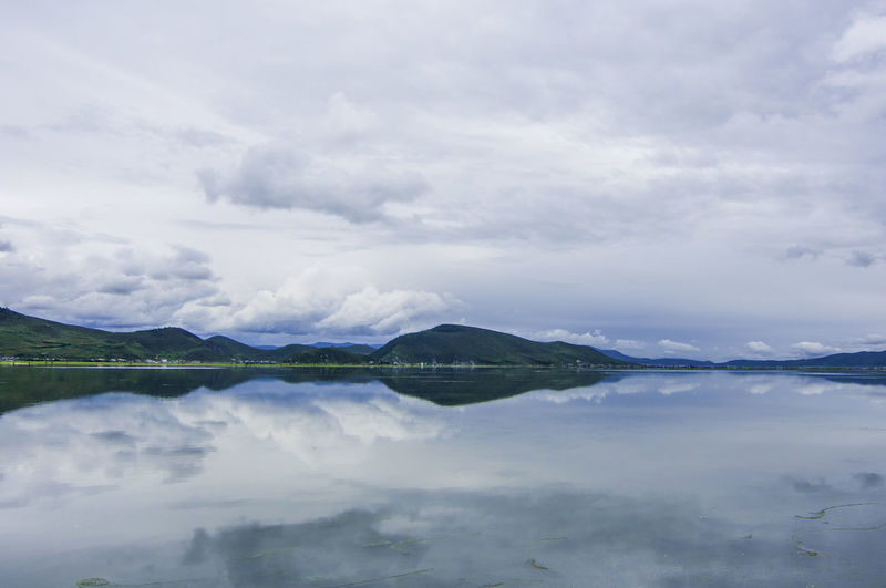 Scenic view of cloudy sky reflecting on calm lake