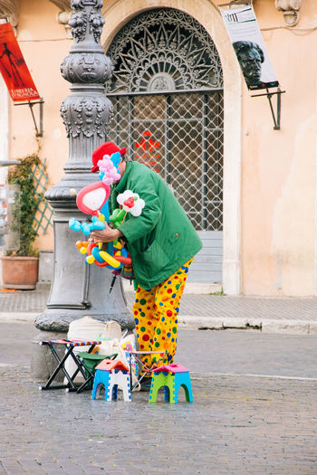 Clown Holding Balloons And Toys On Footpath