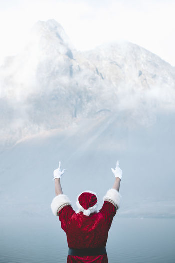 Rear view of man wearing santa claus costume looking at lake during foggy weather