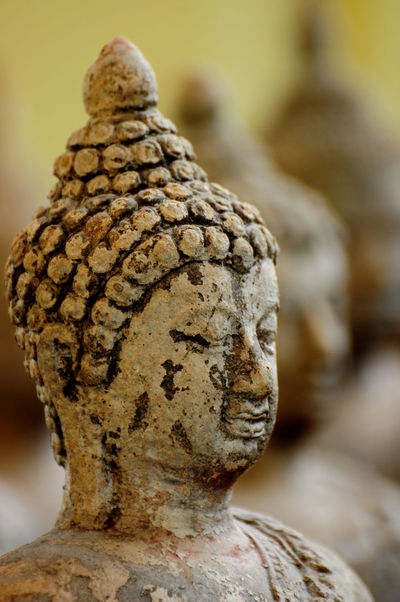Faces of small ancient Buddha image in calm posture. Antique Archaic Arrangement Art And Craft Baked Clay Clam Close-up Craft Day Faithful Focus On Foreground Headshot Human Representation No People Old Religion Sculpture Spirituality Statue Stone Stucco