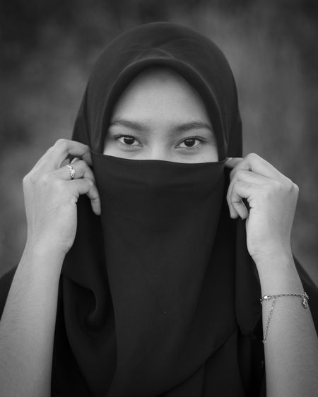 Portrait of beautiful young woman hiding face covered with hand