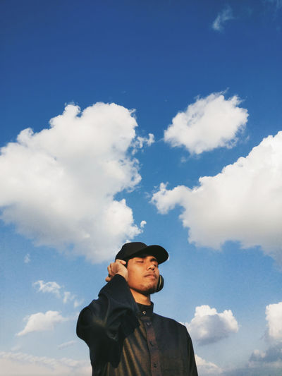 Low angle view of man listening music against sky