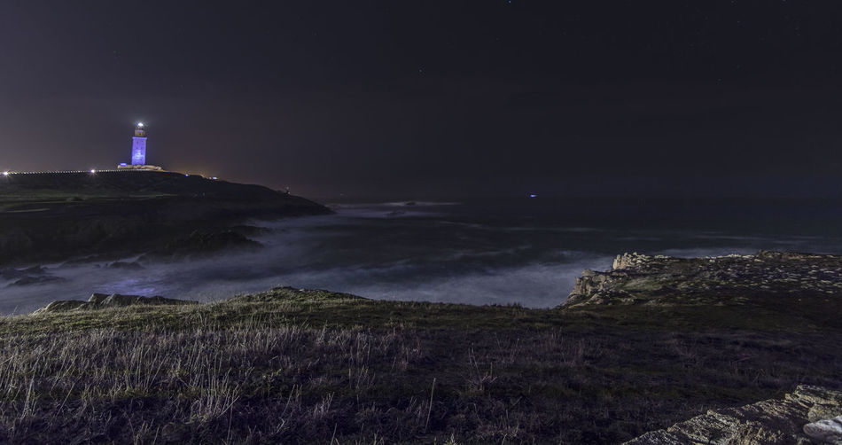 A Coruña roman lighthouse Architecture Beauty In Nature Building Exterior Built Structure Direction Grass Guidance Horizon Over Water Illuminated Landscape Lighthouse Nature Night No People Outdoors Scenics Sea Sky Tranquil Scene Tranquility Water HUAWEI Photo Award: After Dark