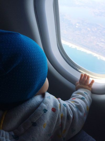 Close-up of baby boy looking through airplane window