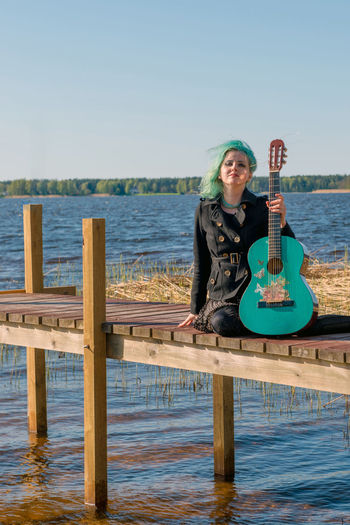Hipster young woman with turquoise guitar sitting on pier over lake