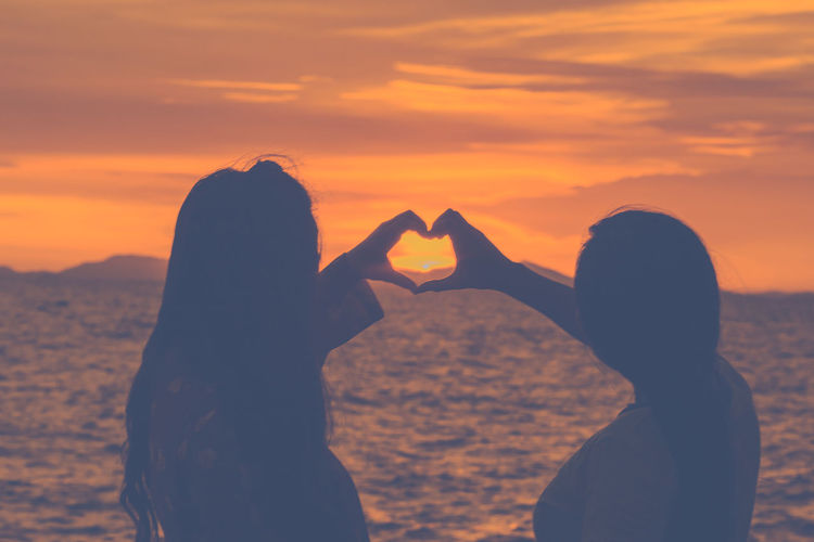Silhouette friends making heart shaped while standing by sea against orange sky
