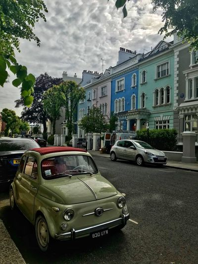 Cars on street by buildings in city against sky