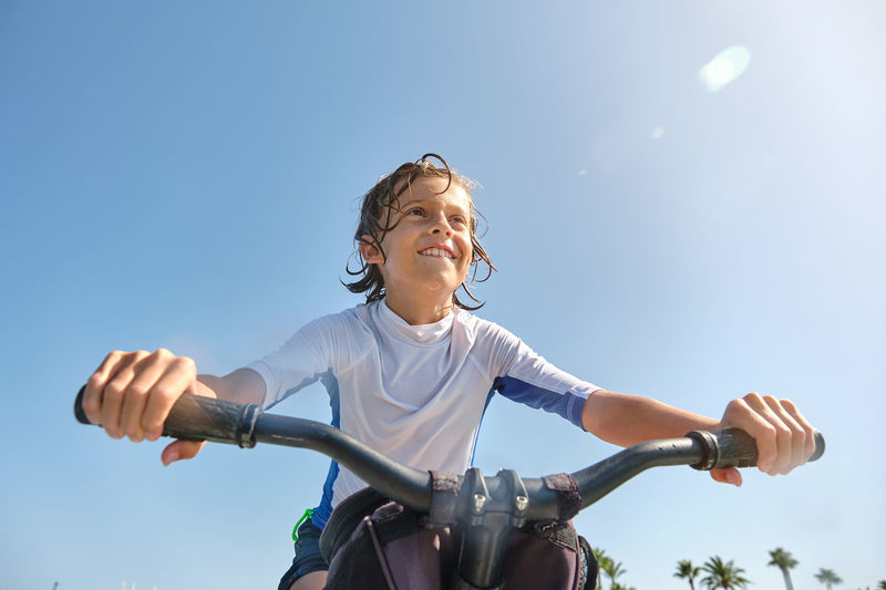 Low angle view of woman riding bicycle against clear sky