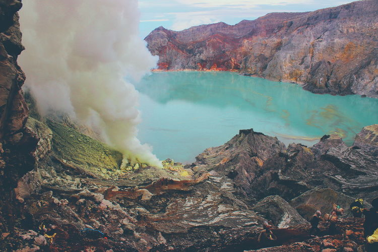 This is Mt. Ijen in Banyuwangi, Jawa Timur. Gunung Ijen which has a one-kilometre-wide turquoise-coloured acidic crater lake. The lake is the site of a labour-intensive sulfur mining operation, in which sulfur-laden baskets are carried by hand from the crater floor. The work is paid well considering the cost of living in the area, but is very onerous. Beautiful Blue Fire INDONESIA Beauty In Nature Day Ijen Ijen Crater Landscape Molten Mountain Nature No People Outdoors Power In Nature Rock - Object Sky Smoke - Physical Structure Sulfur  Volcanic Crater Volcano Water