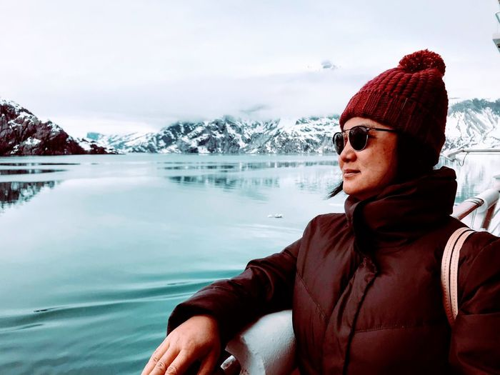 Woman wearing sunglasses by sea and snowcapped mountains against cloudy sky