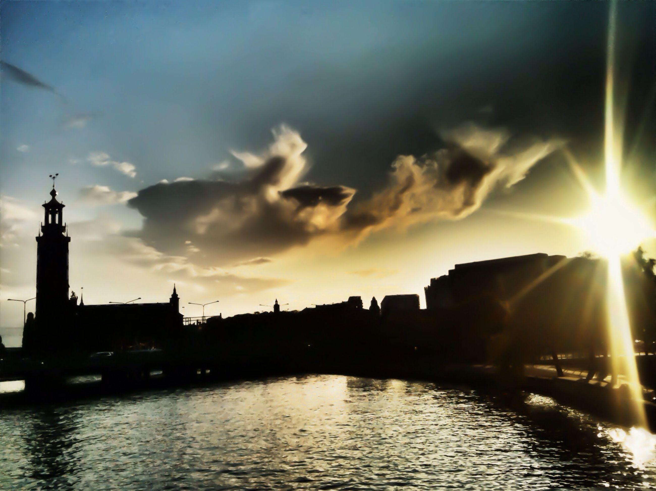 architecture, built structure, sunset, building exterior, waterfront, water, sky, sun, river, silhouette, cloud - sky, city, sunbeam, reflection, sunlight, bridge - man made structure, lens flare, cloud, connection, outdoors