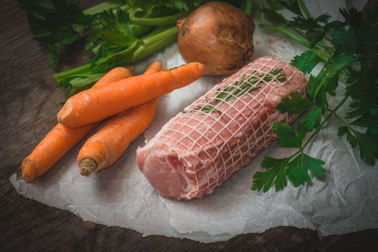 High angle view of vegetables and meat on wooden table