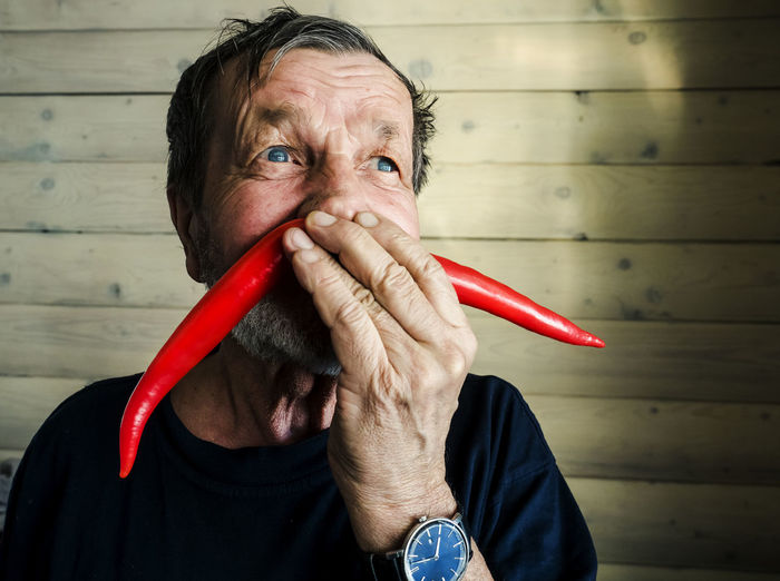 Close-up of senior man making mustache with red chili peppers