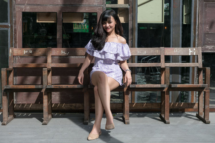 Portrait of happy woman sitting on bench