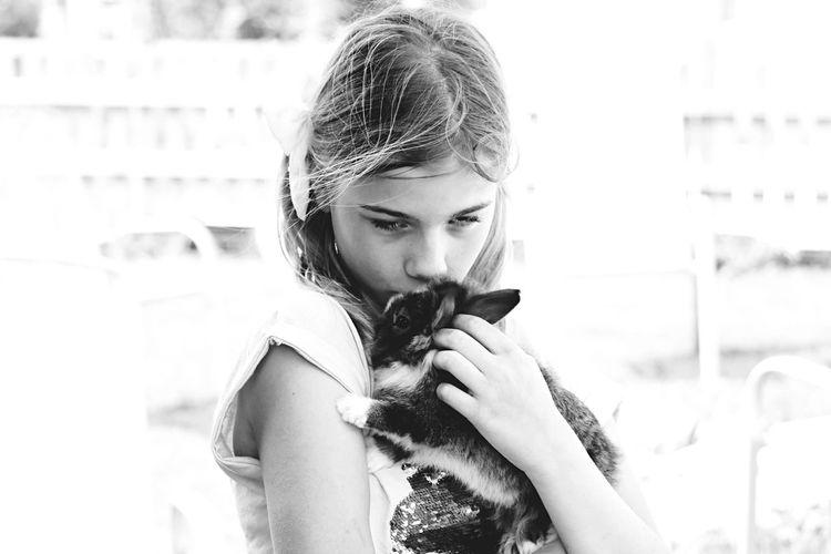 Girl kissing rabbit outdoors