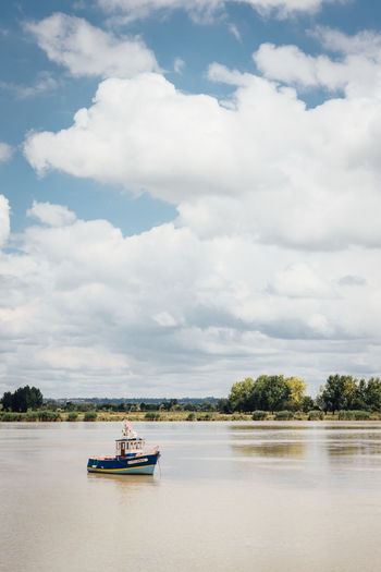 Fishing Fishing Boat Cloud - Sky Nautical Vessel Water Transportation Sky Mode Of Transportation Waterfront Nature Day Tree Scenics - Nature River Beauty In Nature Travel Plant Tranquil Scene Outdoors Tranquility