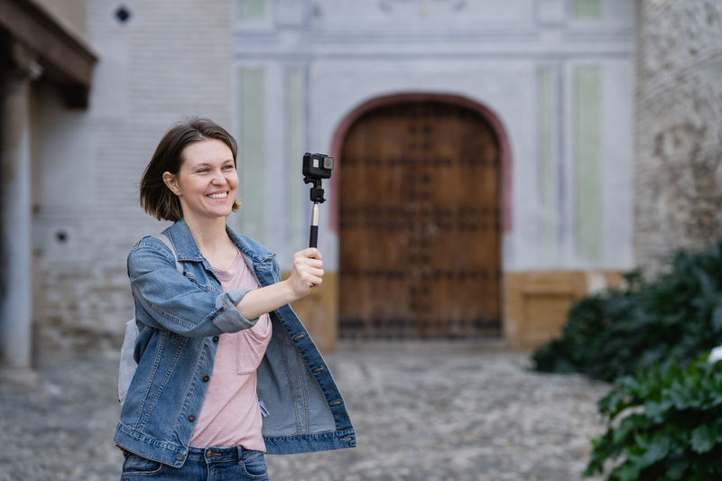 Woman photographing while standing by building