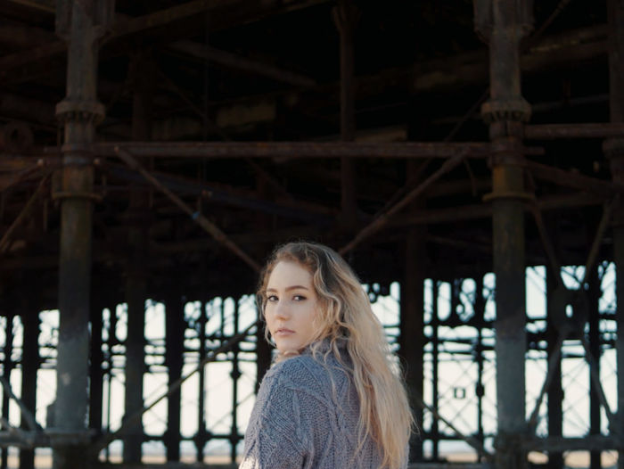 Portrait of woman standing against pier at beach