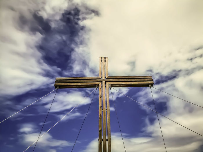 Low angle view of cross against sky