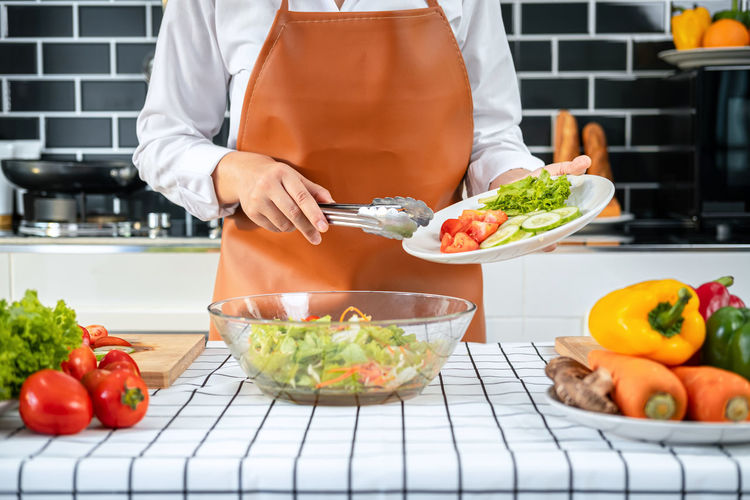 Midsection of man preparing food in kitchen at home