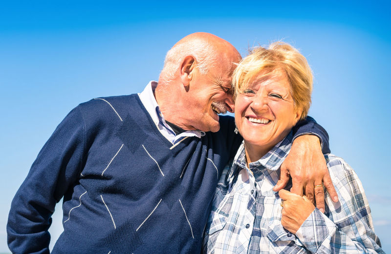 Senior Couple Kissing Against Blue Sky