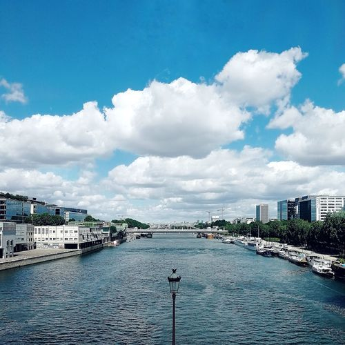 Scenic view of river by city buildings against sky