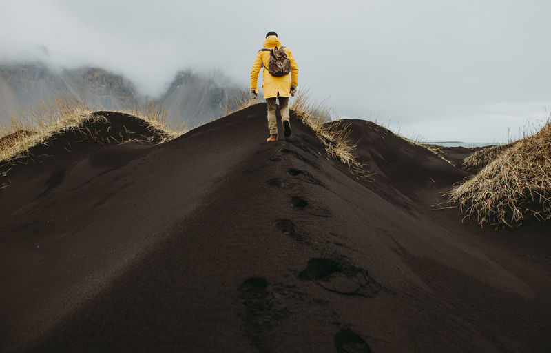 Man on black sand in desert
