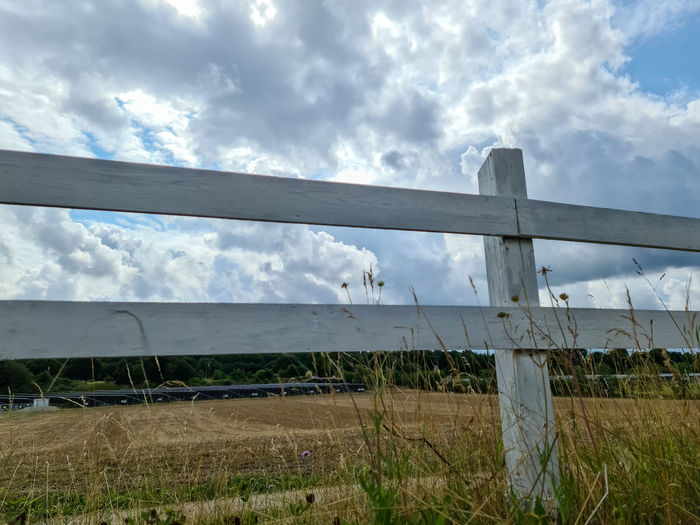 Low angle view of fence on field against sky