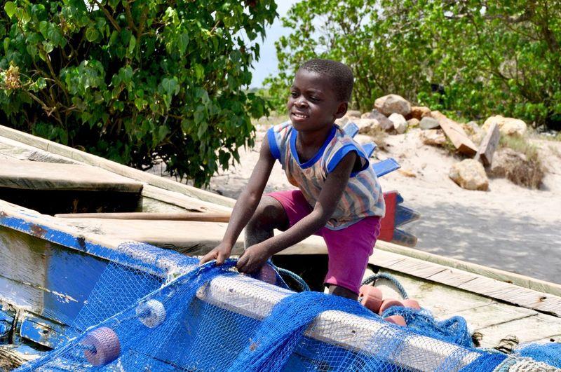 Smiling kid holding fishing net at beach