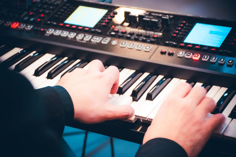 Cropped hands of man playing piano at home