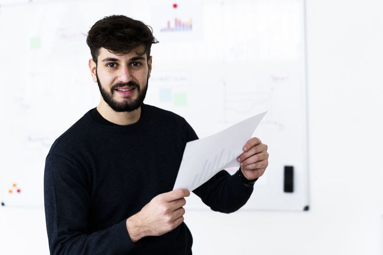 Portrait of young man holding paper