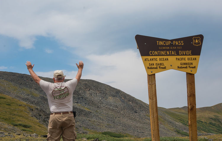 Jul 2018 - Tincup Pass, Colorado USA Continental Divide Tincup Pass Arms Raised Casual Clothing Cloud - Sky Coloradophotographer Environment Human Arm Lifestyles Mountain Nature One Person Outdoors Real People Sign Sky Standing Tincup Western Script