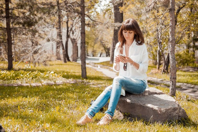 Mid adult woman using phone in park during sunny day