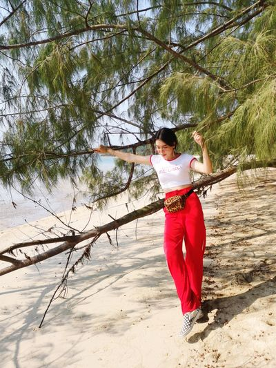Full length of woman standing by tree