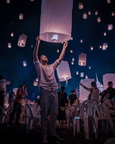 Low angle view of people with paper lanterns at night