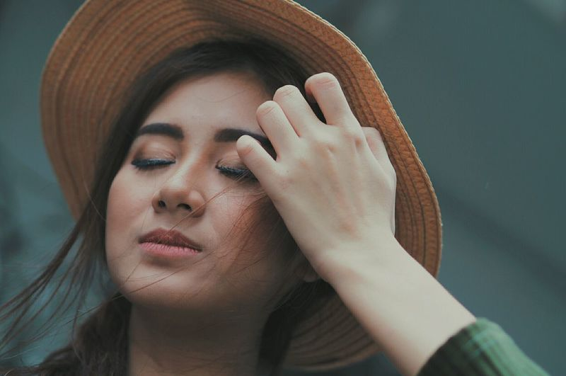 Close-up of woman wearing hat at city