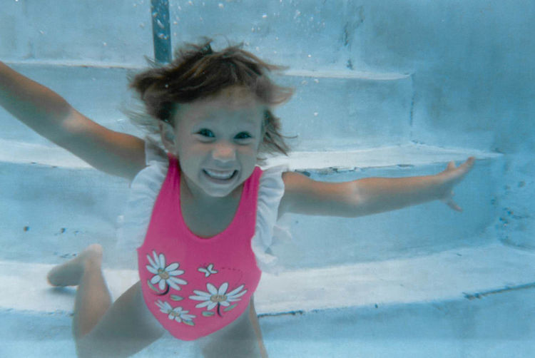 Portrait of cute girl swimming in pool