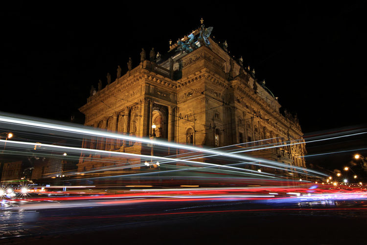 Light trails on road against historic building at night
