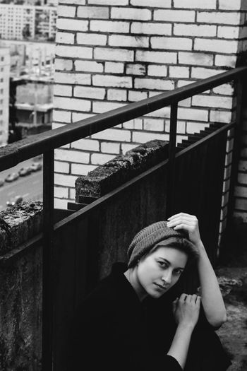 High angle portrait of young woman sitting by weathered wall