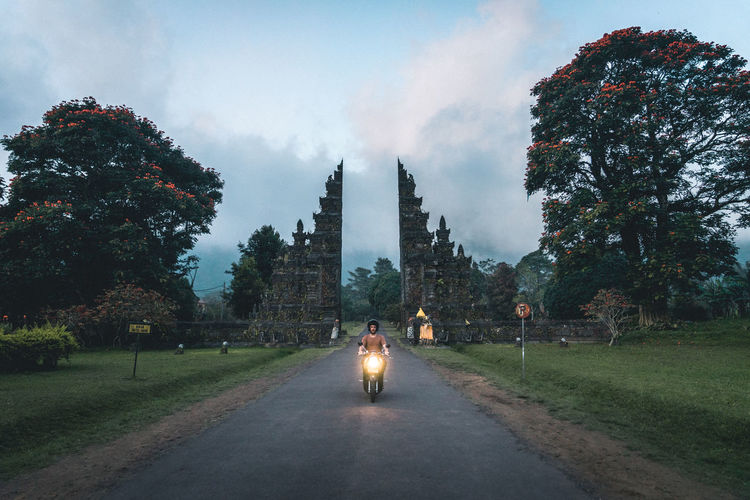 Man driving through a Balinese gate on a motorbike while road-tripping the island Backpacking Bali Bali, Indonesia Driving Freedom Gate INDONESIA Lifestyle Road Scooter Travel Travelling Bali Gat Balinese Bike Instagram Spot Motorbike Motorbike Lights Road Trip Roadtrip Roadtrippin Street Travel Lifes Traveller Travelling Photography Fresh On Market 2017 Go Higher #FREIHEITBERLIN The Traveler - 2018 EyeEm Awards Summer Road Tripping