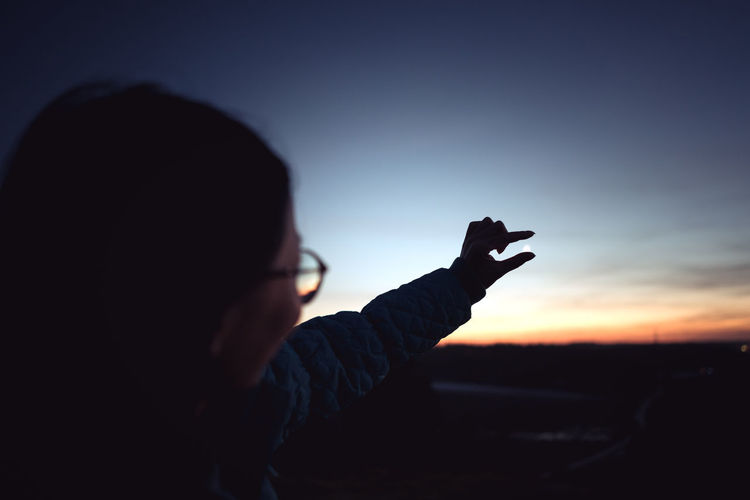 Woman gesturing against sky during sunset